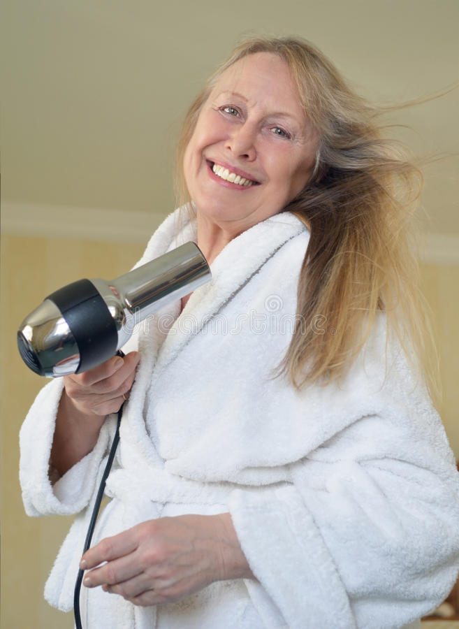 Woman blow drying her hair royalty free stock images