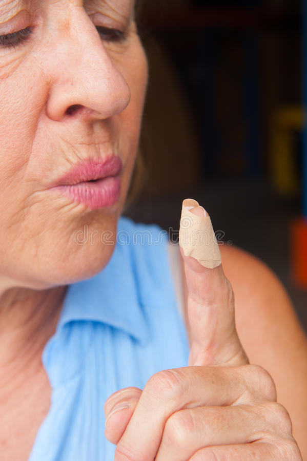 Woman blowing band aid finger wound. Portrait mature woman in pain, hurt and suffering, close up of band aid on injured finger wound stock images