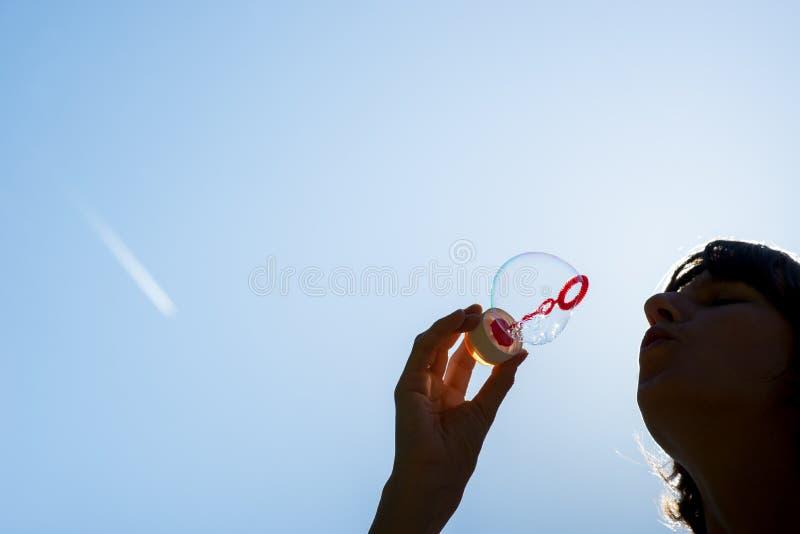 Woman blowing bubbles against a blue sky stock photos