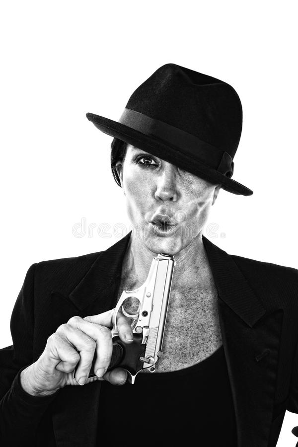 Woman blowing on the end of a smoking gun. Woman blowing on the barrel end of a smoking gun stock photo