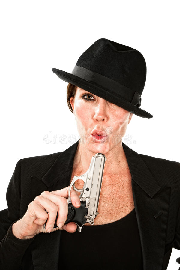 Woman blowing on the end of a smoking gun. Woman blowing on the barrel end of a smoking gun royalty free stock photo
