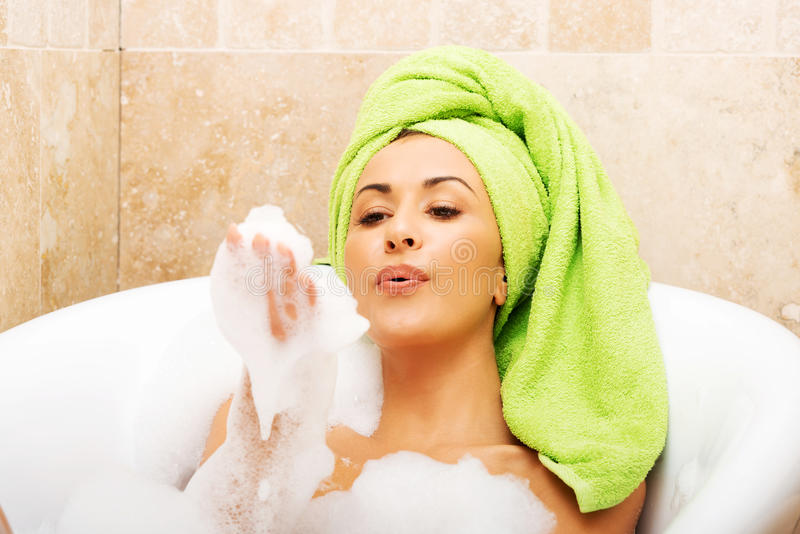 Woman blowing a foam, relaxing in bath stock images
