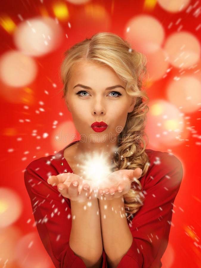 Woman blowing magic on the palms of her hands. Lovely woman in red dress blowing magic on the palms of her hands stock photography