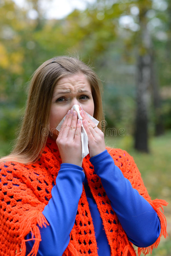 Woman blowing nose into tissue stock photos