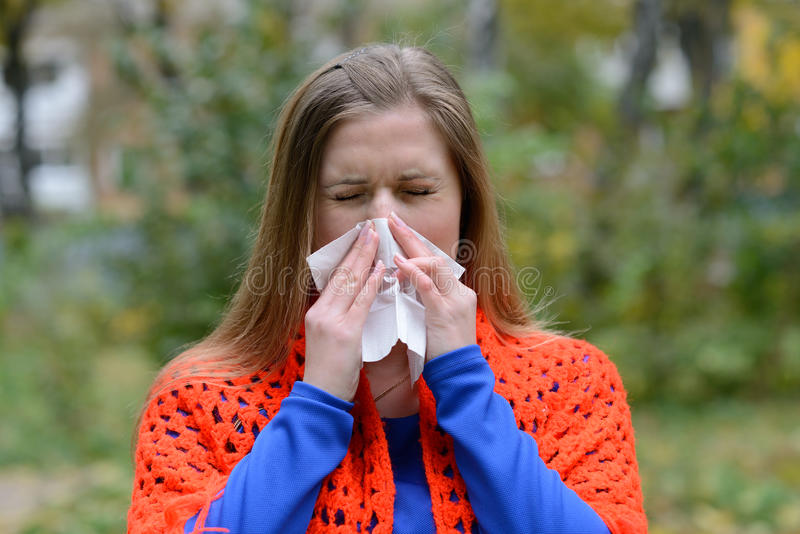 Woman blowing nose into tissue royalty free stock photos