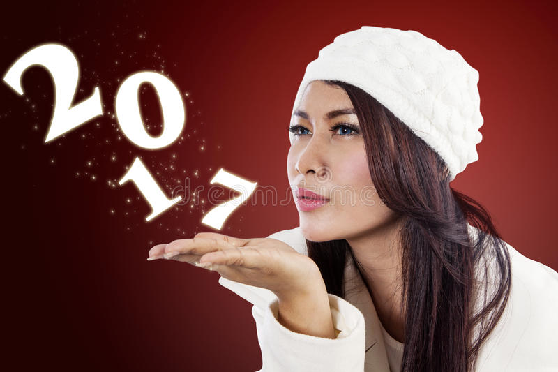Woman blowing numbers 2017 on her palm royalty free stock image