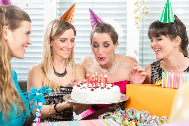 Woman blowing out candles on her birthday cake while celebrating stock image