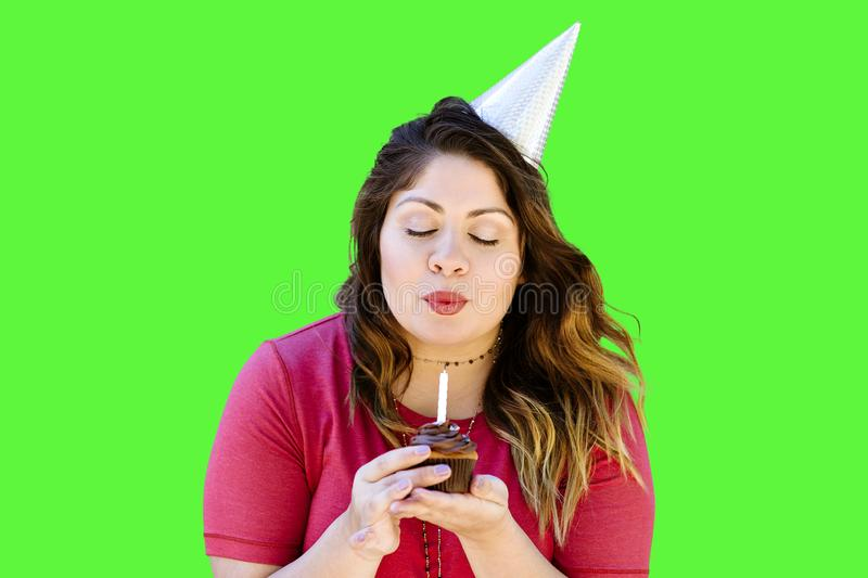 Brunette Female Blows Out the Candle On Her Birthday Cupcake. Woman blowing out her birthday candle on a chocolate cupcake on green screen stock photography
