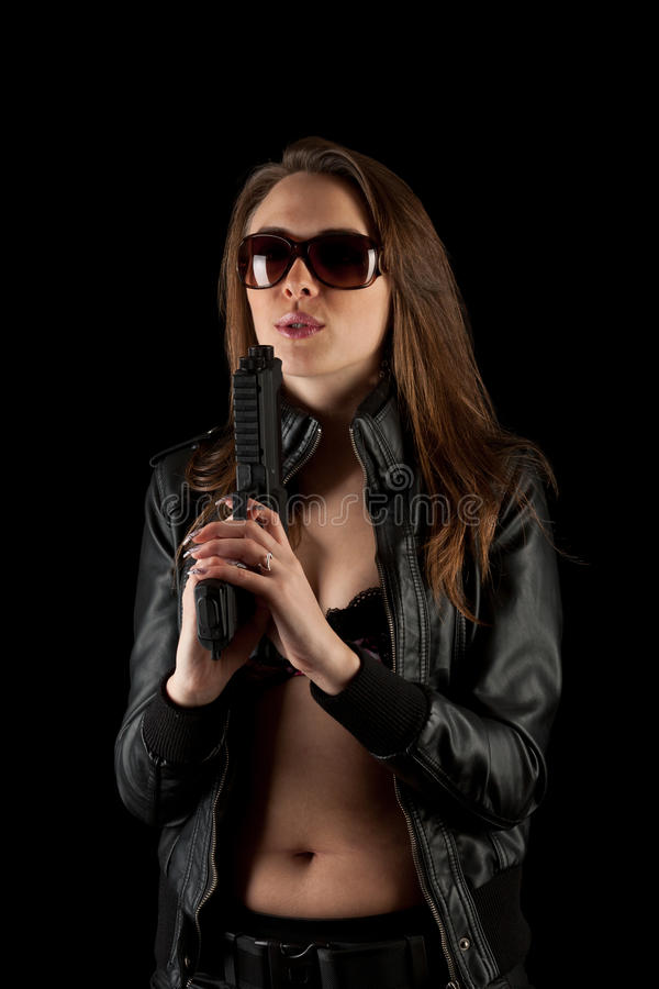 Woman blowing on the smoke. Beautiful woman holding a pistol and blowing on the smoke coming out of the barrel royalty free stock photography