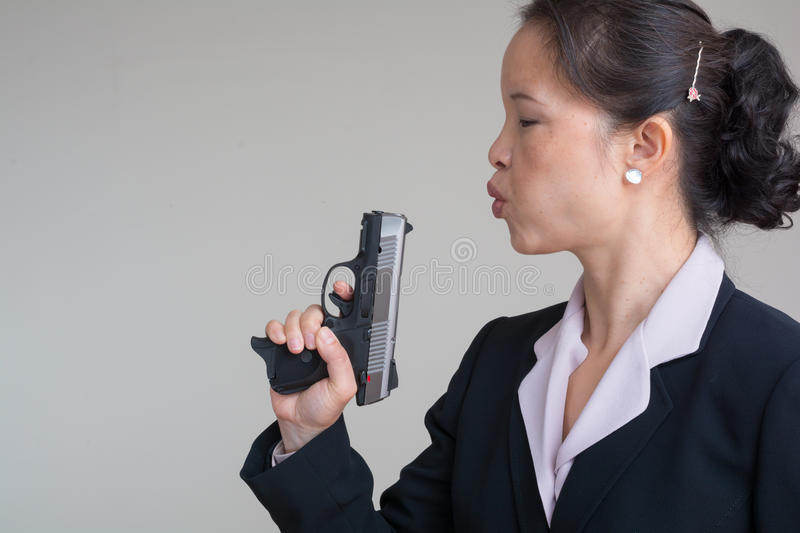 Woman blowing smoke off a hand gun. Woman in business suit blowing smoke off a fired hand gun on grey background royalty free stock photos