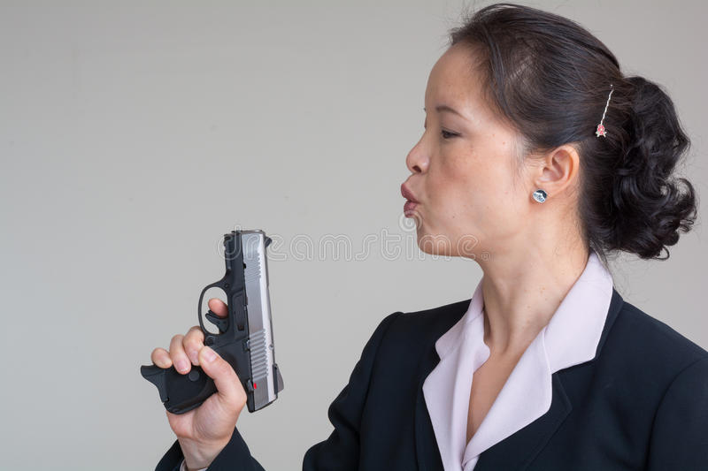 Woman blowing smoke off a hand gun. Woman in business suit blowing smoke off a fired hand gun on grey background stock photos
