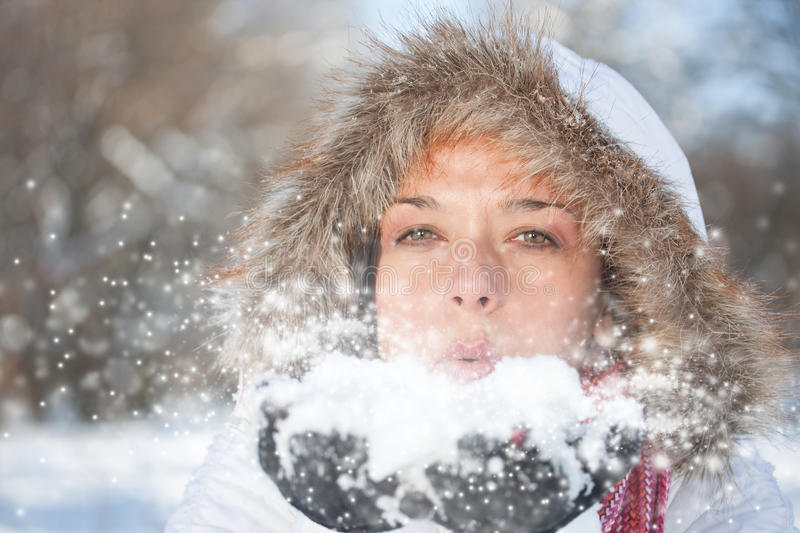 Woman blowing snow stock image