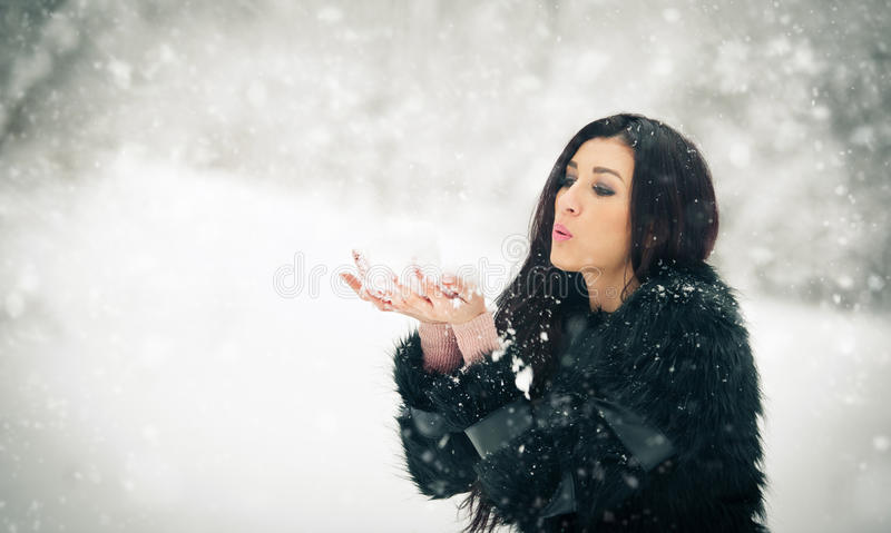 Woman blowing snow from her hands enjoying the winter. Happy brunette girl playing with snow in the winter landscape stock image