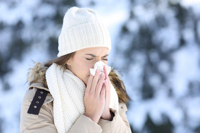 Woman blowing in a tissue in a cold snowy winter royalty free stock photo