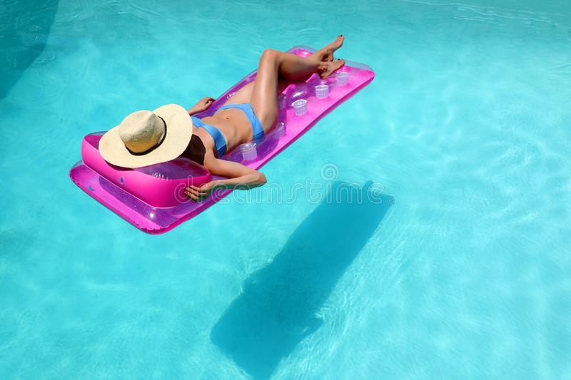 Woman in blue bikini and straw hat floating in turquoise pool royalty free stock images