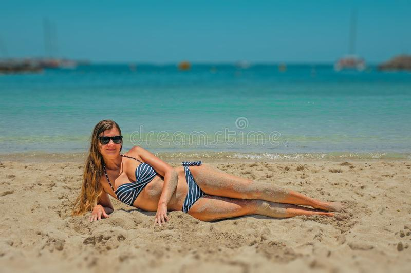 Woman in Blue and Black Bikini Lying on Beach Sand royalty free stock image