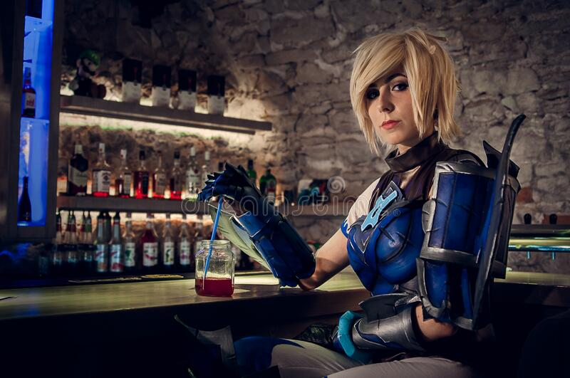 Woman in Blue and Black Mascot Sitting Near Drinking Glass stock images