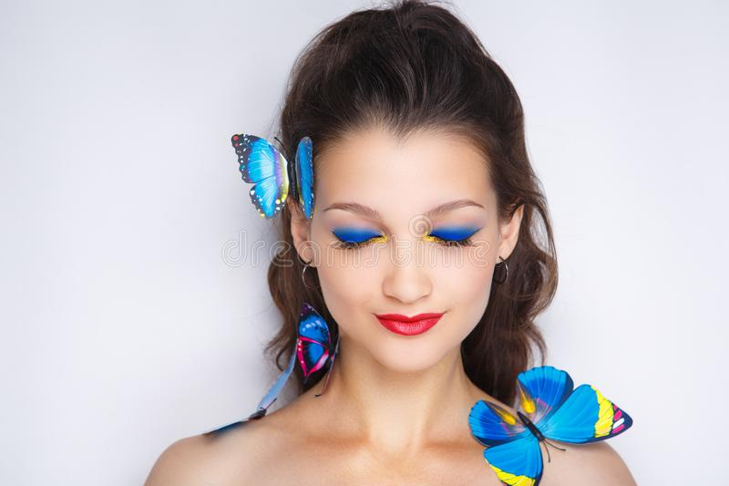 Woman blue butterfly. Bright blue butterflies seating on woman head, hair. Oriental beauty girl professional makeup. Portrait of a beautiful lady. Young girl stock image