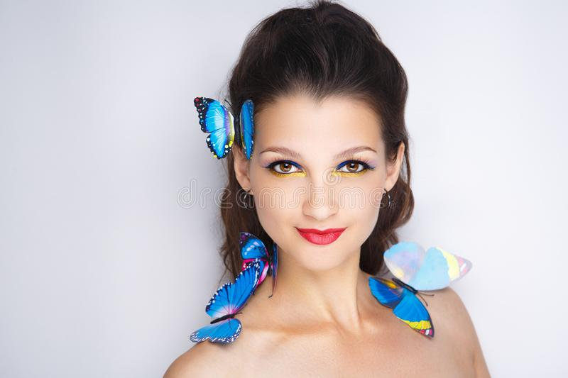 Woman blue butterfly. Bright blue butterflies seating on woman head, hair. Oriental beauty girl professional makeup. Portrait of a beautiful lady. Young girl royalty free stock photos