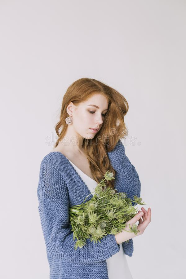 Woman in Blue Cardigan Holding Green Flowers stock image