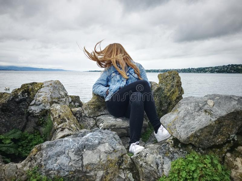 Woman With Blue Denim Collared Button-up Jacket and Black Jeans Sitting on Gray Rock Watching Lakeview stock photography