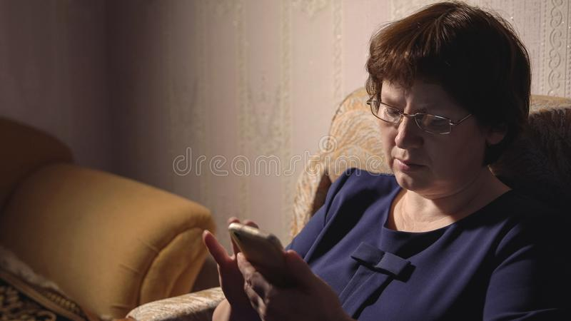 Woman in a blue dress and glasses sits in an armchair with a phone royalty free stock images