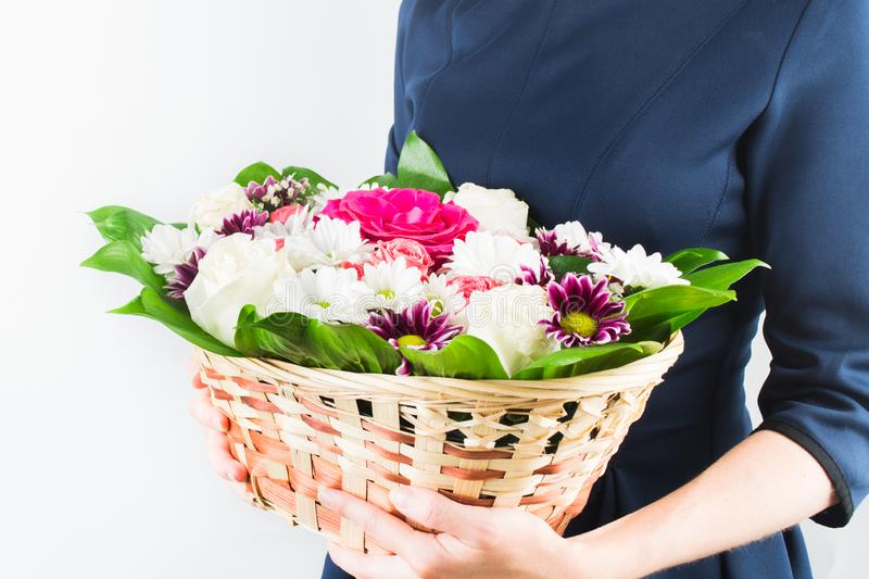 Woman in blue dress holding flowers in wicker basket in hands. White background royalty free stock image