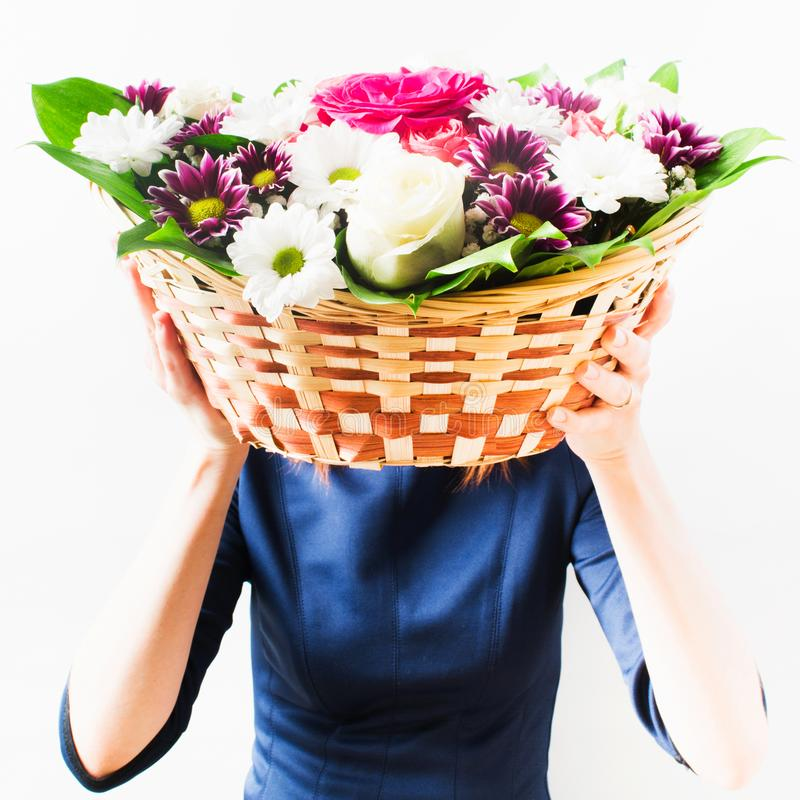 Woman in blue dress holding wicker basket with flowers in her hands instead of head. Isolated background royalty free stock photography
