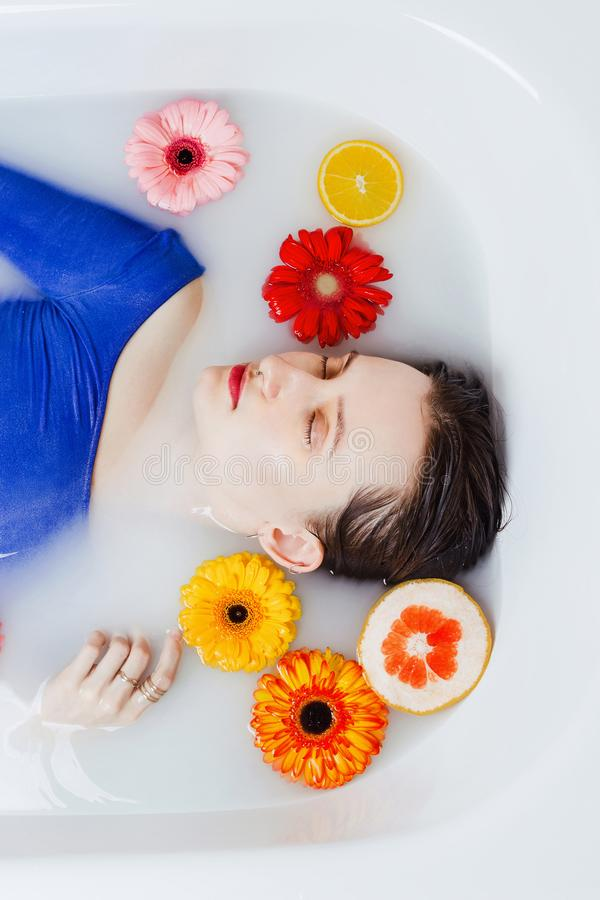 Woman in blue dress lying in bathtub filled with white water royalty free stock image