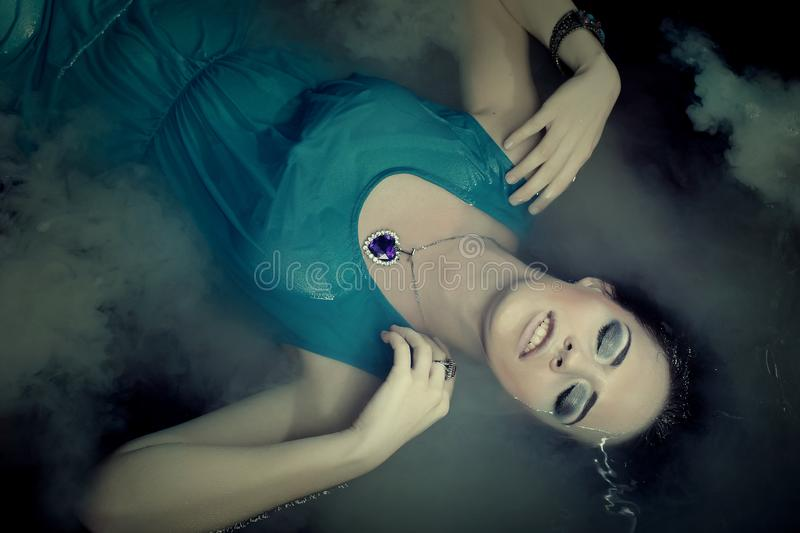 Woman in blue dress lying in water. Young woman in blue dress lying in water stock photography