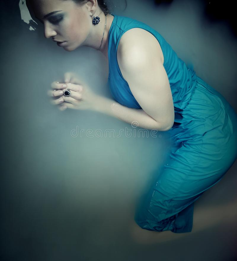 Woman in blue dress lying in water. Young woman in blue dress lying in water stock photos
