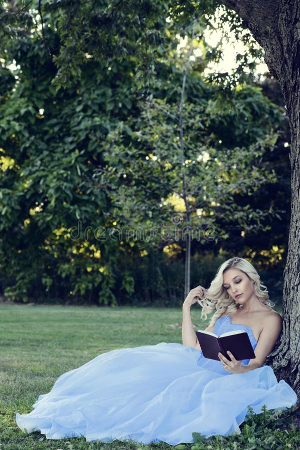 Woman in blue dress reading a book leaning on tree stock photography