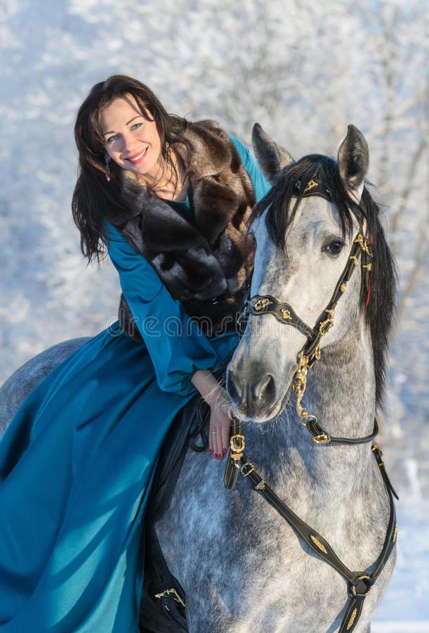 Woman in a blue dress riding on a grey stallion stock photos
