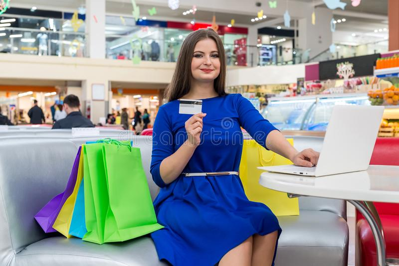 Woman in blue dress showing credit card. Beautiful woman in blue dress showing credit card stock images