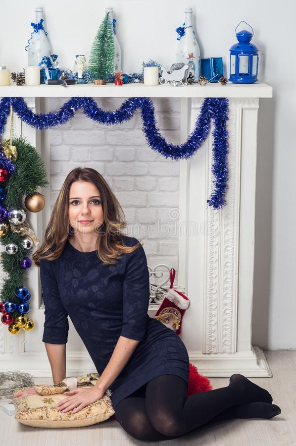 Woman in a blue dress sitting in front of a white decorative fireplace with New Year decorations. Christmas home decoration stock photography