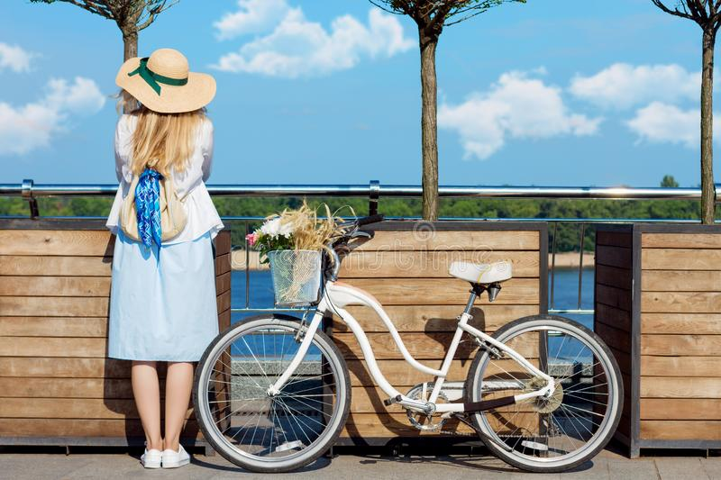 Woman in blue dress, straw hat close to bicycle with basket of flowers royalty free stock photo
