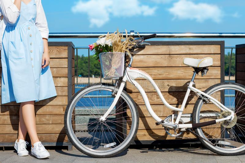 Woman in blue dress, straw hat close to bicycle with basket of flowers stock image