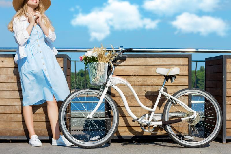 Woman in blue dress, straw hat close to bicycle with basket of flowers stock images