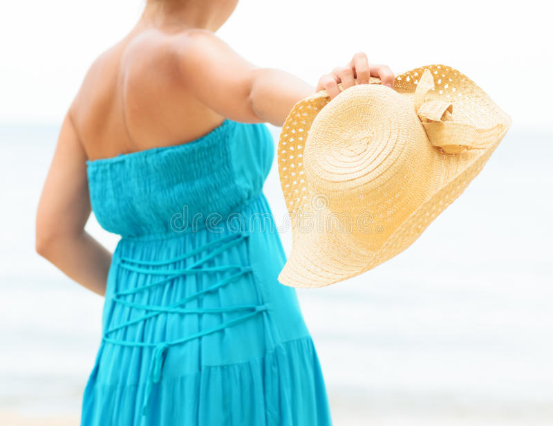Woman in blue dress throws hat on the beach