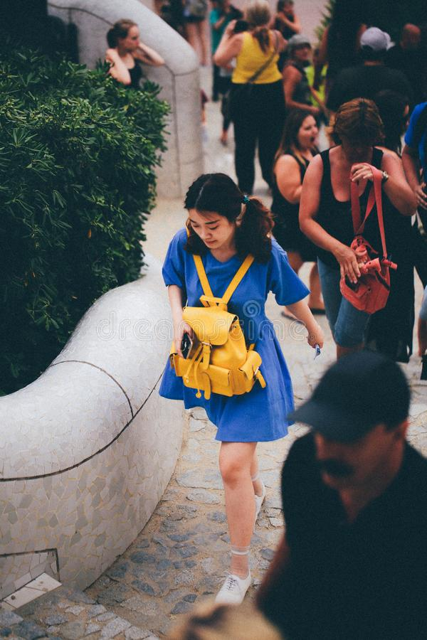 Woman in Blue Dress With Yellow Knapsack Walking Near People royalty free stock image