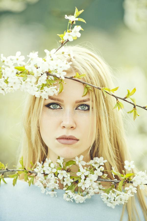 Woman with blue eyes posing with white, blossoming flowers. Woman with blue eyes, adorable face, stylish makeup and long, blond hair posing with white stock photos