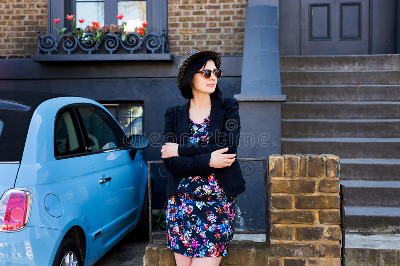Woman in blue flowered dress, sunglasses and hat stock photography