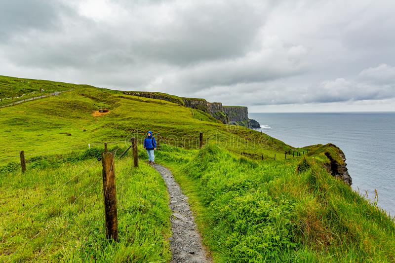 Woman in blue jacket enjoying the coastal walk route from Doolin to the Cliffs of Moher. Geosites and geopark, Wild Atlantic Way, spring rainy day in the royalty free stock photo