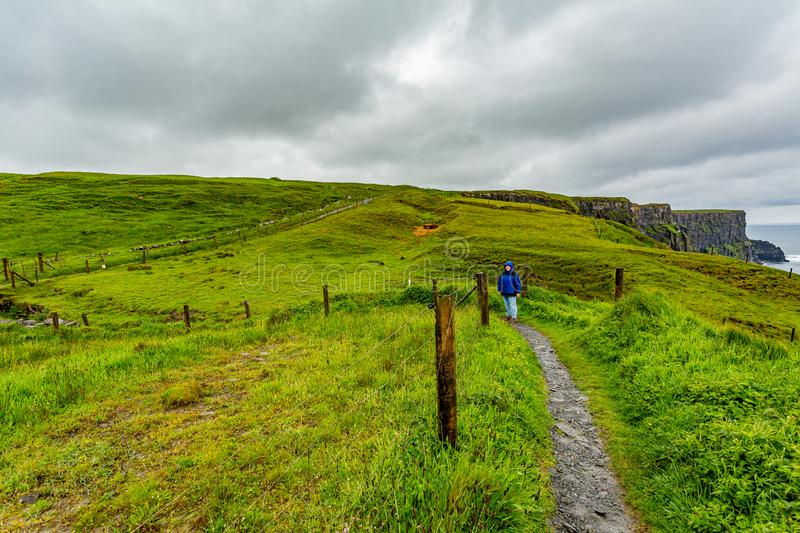 Woman with blue jacket hiking from Doolin to the Cliffs of Moher along the coastal walk route. Geosites and geopark, Wild Atlantic Way, spring rainy day in the royalty free stock photography