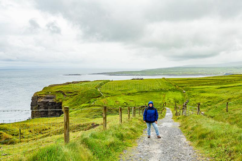 Woman in blue jacket pausing on the coastal route walk from Doolin to Cliffs of Moher. Geosites and geopark, Wild Atlantic Way, spring cloudy day in the stock photo