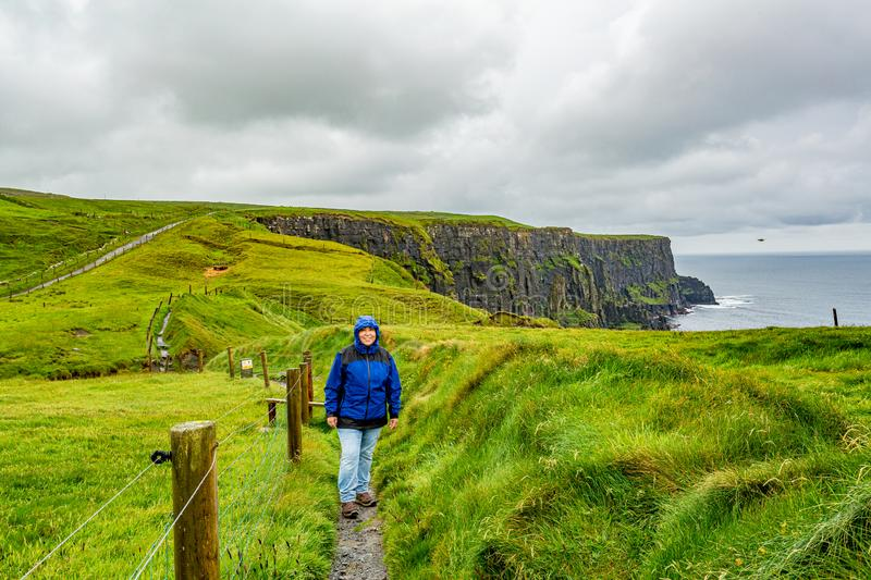 Woman in blue jacket walking the coastal walk route from Doolin to the Cliffs of Moher. Geosites and geopark, Wild Atlantic Way, spring rainy day in the stock images