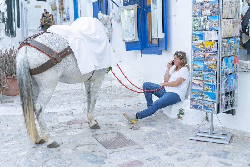 Woman in blue jeans sitting on step outside whitewashed shop with blue windows holding red reins for whate horse stock photos