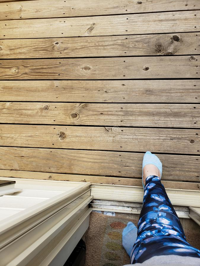 Woman in blue leggings and blue ankle socks stepping out of a door onto a wood porch stock images