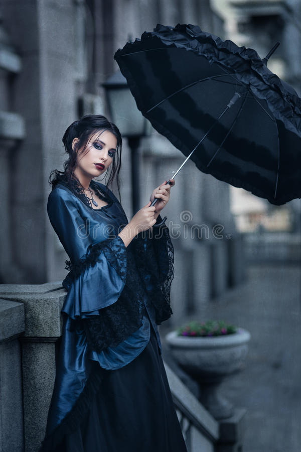 Woman in blue near old building stock images