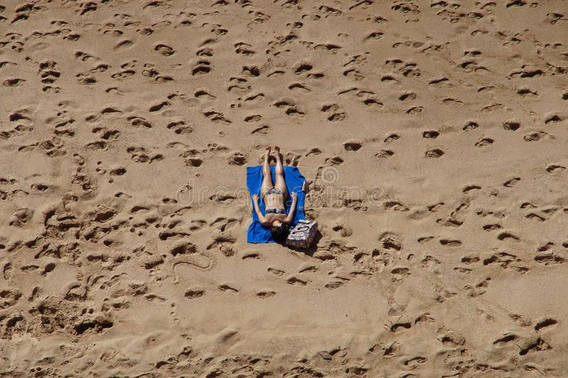 Woman in Blue 2-piece Set Lying on Blue Blanket at Beach on Aerial Photo royalty free stock photography